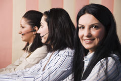 Friendly customer service teamwork women. Friendly team of customer service team standing in line, focus on first brunette woman which looked you and smiling royalty free stock photos