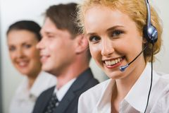 Friendly customer support. A friendly smiling customer support operator on a background of two business people Stock Image
