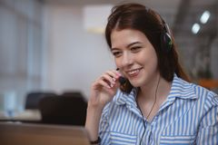 Friendly customer support operator with headset working at call center stock photos