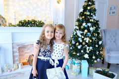 Friendly cute sisters pose for camera, hold gifts in hands , smi. Beautiful female sisters pose for camera, hold gifts and white lantern in hands , smiling and stock photo