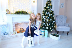 Friendly cute sisters pose for camera, hold gifts in hands , smi. Beautiful female sisters pose for camera, hold gifts and white lantern in hands , smiling and royalty free stock photos