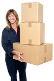 Friendly delivery woman with three packed cartons Stock Image