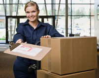 Friendly delivery woman in uniform stock photography