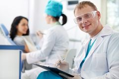 Friendly dentist. A handsome dentist smiling at camera with a nurse and a patient in the background Royalty Free Stock Photos