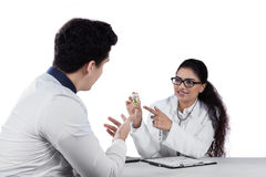 Friendly dentist explaining drugs. Young doctor holding pill on a little bottle and explain to her patient, isolated on white Royalty Free Stock Photos