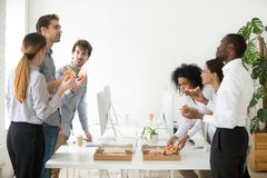 Friendly diverse business team talking eating pizza together in. Friendly diverse business team members or multi-ethnic colleagues eating sharing pizza together Stock Images