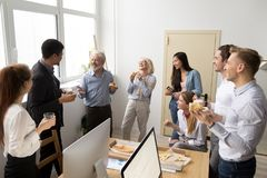 Friendly diverse business team talking and laughing eating pizza. Friendly diverse business team of young and senior colleagues eating pizza together in office Stock Photos