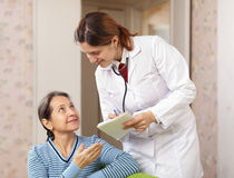 Friendly doctor asks mature patient feels Royalty Free Stock Photography