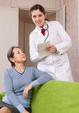Friendly doctor asks mature patient feels Stock Images