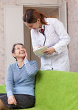 Friendly doctor asks mature patient feels Stock Image