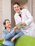 Friendly doctor asks  mature patient feels Stock Photo