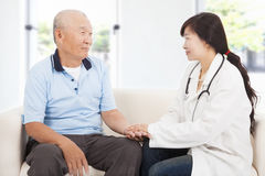Friendly doctor caring senior man indoor room. Friendly doctor caring senior men indoor room at home Stock Photos