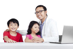 Friendly doctor with children 2. Friendly doctor with children smiling at camera, isolated on white background Royalty Free Stock Images