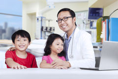 Friendly doctor with children 1. Friendly doctor with children smiling at camera, shot in hospital Royalty Free Stock Images
