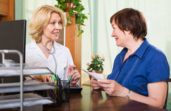 Friendly  doctor consulting female patient Stock Photo