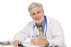 Friendly Doctor Doing Paperwork Royalty Free Stock Photos
