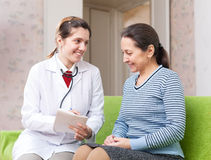 Friendly doctor examining mature woman Royalty Free Stock Photos