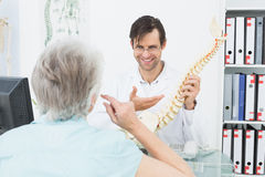 Friendly doctor explaining spine to a senior patient Royalty Free Stock Photos