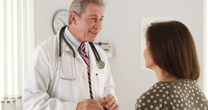 Friendly doctor having a conversation with senior patient Royalty Free Stock Photo