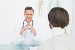Friendly doctor listening to patient with concentration at desk Royalty Free Stock Images