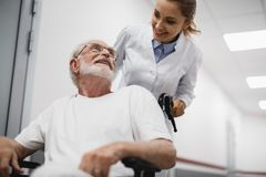 Friendly doctor looking at disabled old man with smile. Low angle portrait of cheerful bearded gentleman sitting in wheelchair while female medic standing behind stock image