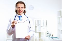 Friendly doctor in medical office Stock Photography