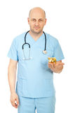 Friendly doctor with piggy bank. Friendly bald doctor holding piggy bank isolate don white background Royalty Free Stock Images