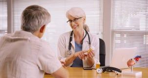 Friendly doctor prescribing medication to elderly patient Stock Image