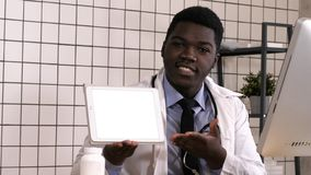 Friendly doctor presenting digital tablet screen. White Display. stock images