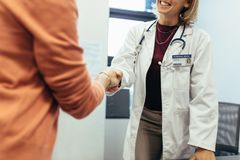 Friendly doctor shaking hands with patient royalty free stock photography