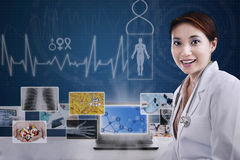 Friendly doctor showing digital x-ray photo on blue Royalty Free Stock Photography