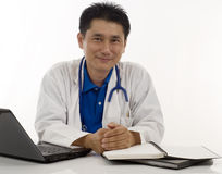 Friendly Doctor sitting at his desk Royalty Free Stock Images