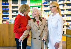 Friendly doctor talking with two elderly women. Friendly female pharmacist in pony tail and eyeglasses talking and laughing together in front of pharmacy counter royalty free stock images