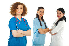 Friendly doctor woman and her team. Friendly doctor woman in front of camera standing with arms folded and her team smiling in background Stock Photography