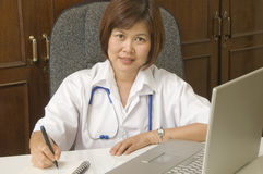 Friendly Doctor writing at her desk Royalty Free Stock Images
