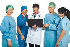 Friendly doctors team with laptop. Friendly doctors using a laptop and a smiling surgeon woman looking at camera isolated on white background Royalty Free Stock Images