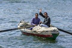 Friendly Egyptian men row their boat on the River Nile near Edfu in Egypt. stock photos