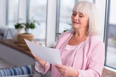 Friendly elderly lady consulting a source Stock Images