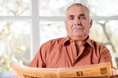 Friendly elderly man sitting reading Stock Photography