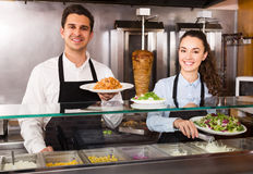 Friendly employees working with kebab Stock Images