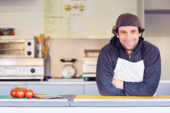 Friendly entrepeneur in his clean takeaway food stall. Entrepeneur looking friendly and confident in his clean food stall where he makes takeaway food Stock Photos