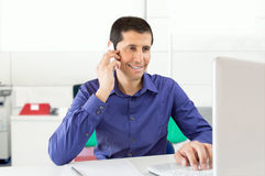 Friendly executive talking by phone at office Royalty Free Stock Image