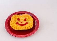 Friendly face on a pie. A pie with a smiling face drawn on it using tomato sauce isolated on a plate on a white background stock photography
