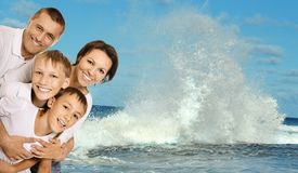 Friendly family on a background of sea wave Royalty Free Stock Photos