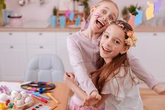 Happy little females looking straight at camera. Friendly family. Beautiful longhaired brunette expressing positivity while embracing her sister stock photo