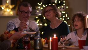 Friendly family celebrates Christmas at the table. Grandpa imposes a salad. Family of vegetarians, healthy lifestyle.  stock video footage