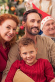 Friendly family celebrating Christmas at home. Happy New Year. Cheerful mother and father are hugging boy and smiling. Grandfather is sitting near them and Royalty Free Stock Image