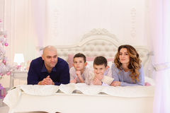 Friendly family chats lying on bed, mom and dad with their child stock photos