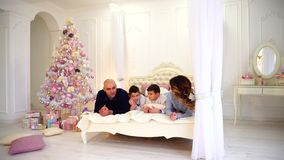 Friendly family chats lying on bed, mom and dad with their children laugh, lying on large bed in bright bedroom with. Merry parents and twin boys, children stock video footage