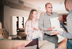 Friendly family couple dissatisfied with service. In furniture store Stock Photography